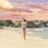Smiling Woman Walking Barefoot On Seashore Near Houses